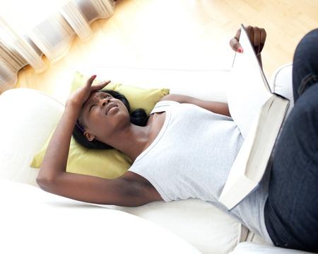 Unhappy woman reading lying on a sofa photo