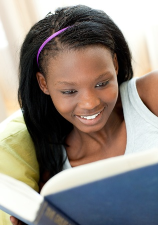 Delighted teen girl studying lying on a sofa photo