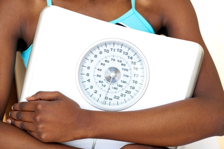 Close-up of a fitness woman with thumb up holding a weight scale Stock Photo - 10094428