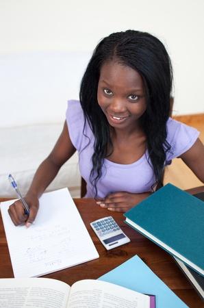 Smiling Afro-American teen girl doing her homework  photo