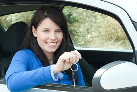 Happy teen girl sitting in her car holding keys photo