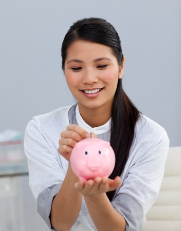 Asserive businesswoman saving money in a piggybank photo