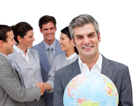 Confident business team looking at the camera with a globe photo