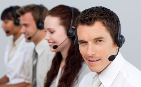 Attractive man working with his team in a call center photo