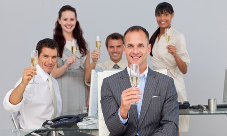 Successful business co-workers toasting with Champagne  photo