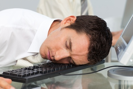 Businessman sleeping on the keyboard in the office photo