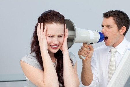 Businessman yelling through a megaphone at a businesswoman photo