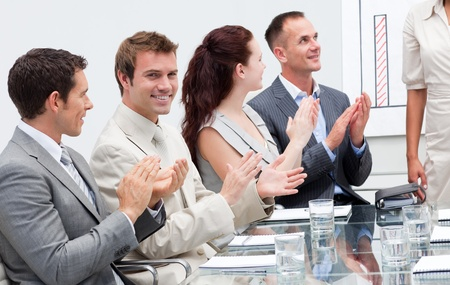 Business people applauding a colleague after giving a presentation photo