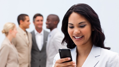Smiling ethnic businesswoman sending a text photo