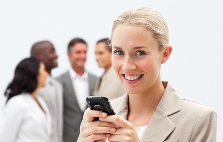 Smiling businesswoman writing a message with a mobile phone Stock Photo - 10093544