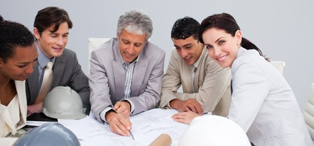 Beautiful female architect studying plans with her colleagues photo