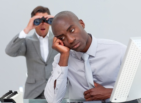 afflict: Afro-american businessman annoyed by a man looking through binoculars Stock Photo