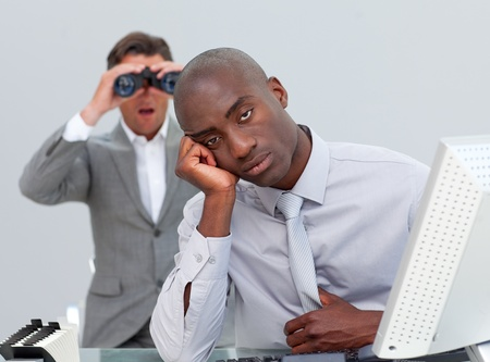 afflict: Ethnic businessman getting bored and his manager looking through binoculars