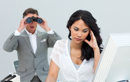 bother: Young businesswoman getting bored and her manager looking through binoculars Stock Photo