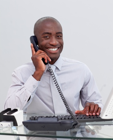 Smiling Afro-American businessman on phone in the office photo