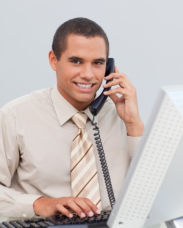 Young businessman talking on phone in the office photo