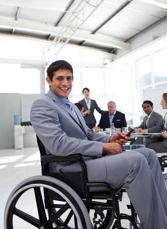 wheelchair man: Young businessman in a wheelchair at a meeting