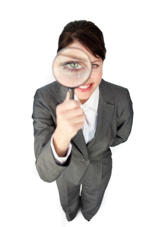 Young businesswoman looking through magnifying glass  photo