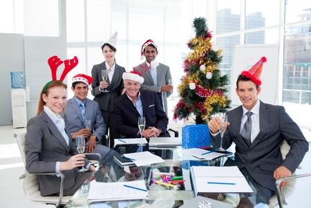 cappello natale: Ritratto di un team d'affari sorridente che indossa novit� cappello di Natale