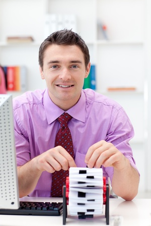 Smiling businessman consulting his business card holder Stock Photo - 10094085