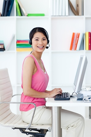 computer operator: Asian businesswoman with headset on at a computer