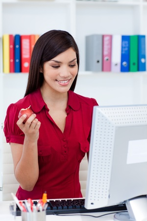 Smiling businesswoman holding a red apple photo