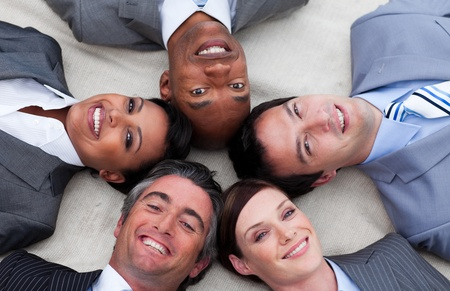 Multi-ethnic business team lying on the floor with heads together photo