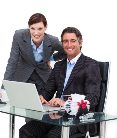 Confident businessman showing something on computer to his colle photo