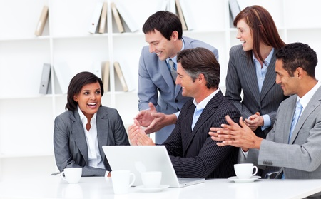 teaming: Laughing businesswoman applauded by her team