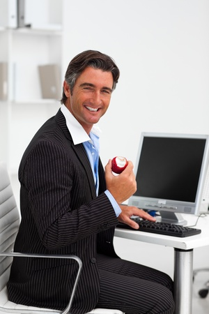 Smiling businessman holding a red apple photo