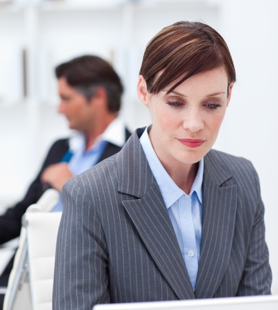 Concentrated businesswoman sitting at office desk photo