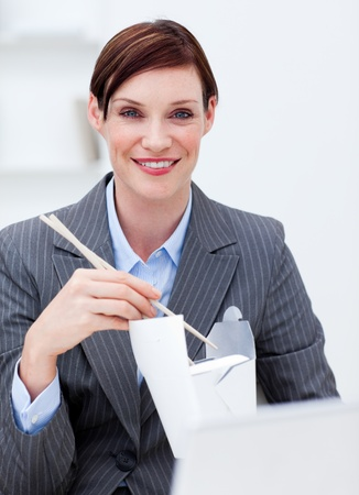 Businesswoman eating chinese food at work photo