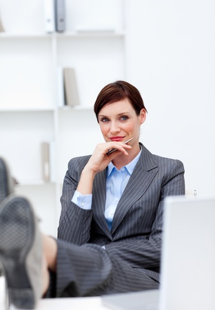 Satisfied Businesswoman sitting in office with feet on desk photo
