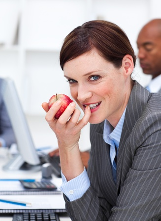 Businesswoman eating a fruit at work Stock Photo - 10094724
