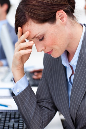 stressed woman: Attractive businesswoman suffering from a migraine