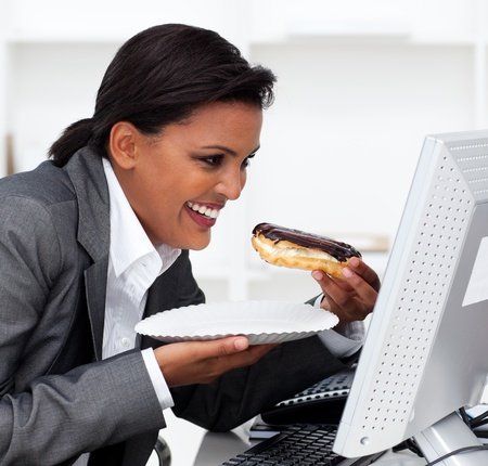 eclair: Close-up of a laughing businesswoman eating a chocolate eclair