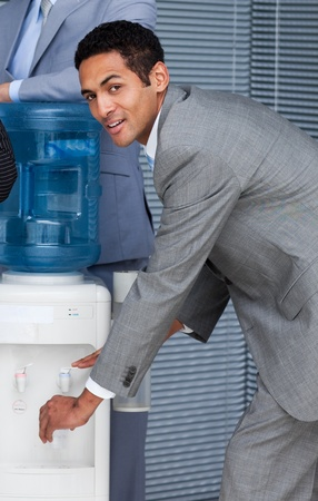 Attractive businessman filling cup from water cooler