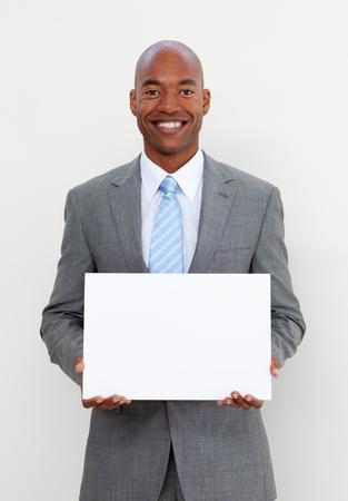Smiling businessman holding white card photo