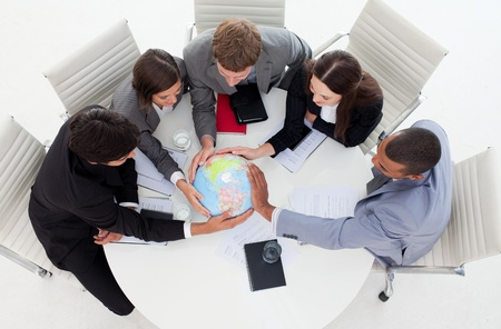 terrestrial globe: Internatonal Business team holding a terrestrial globe