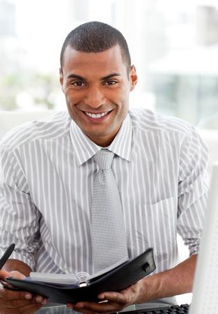 Smiling businessman consulting his agenda Stock Photo - 10093933