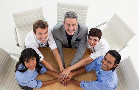 Equipo internacional de negocios con las manos juntas