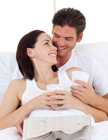 Couple drinking coffee and reading newspaper photo