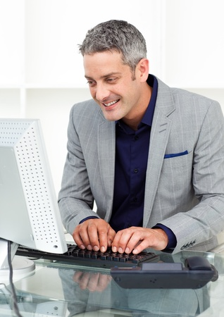 Positive businessman working at a computer  photo
