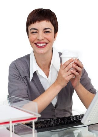 Charming Female executive drinking a coffee at her desk  photo