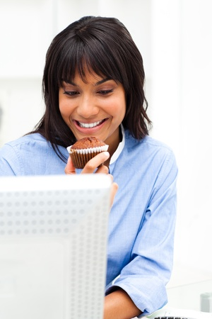 Charming businesswoman eating a muffin Stock Photo - 10096837