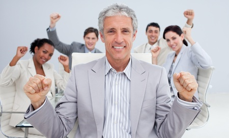 Happy businessman celebrating a sucess with his team photo