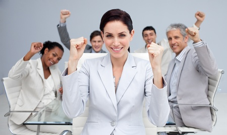Happy business people celebrating a sucess with hands up photo