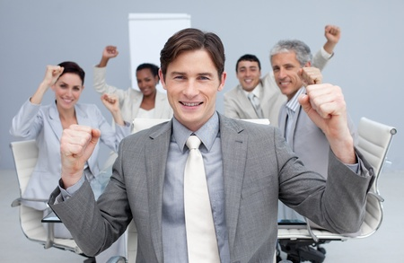 Happy business team celebrating a sucess with hands up photo