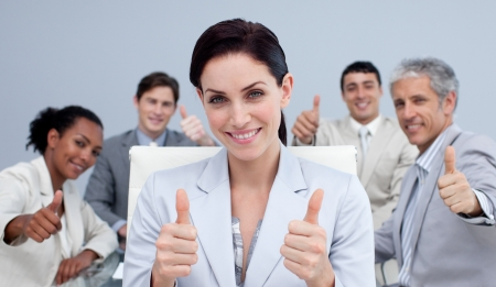 Businesswoman and her team with thumbs up in a meeting photo