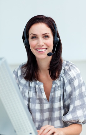 headset woman: Confident businesswoman with headset on working at a computer